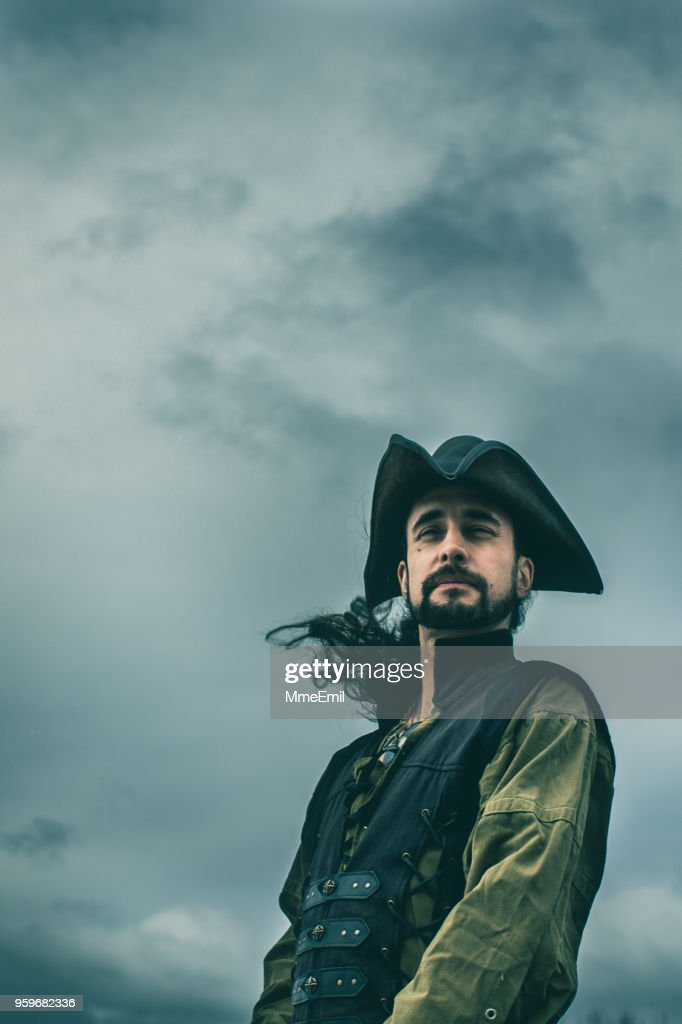 Pirate standing in front of a dramatic sky : Stock Photo