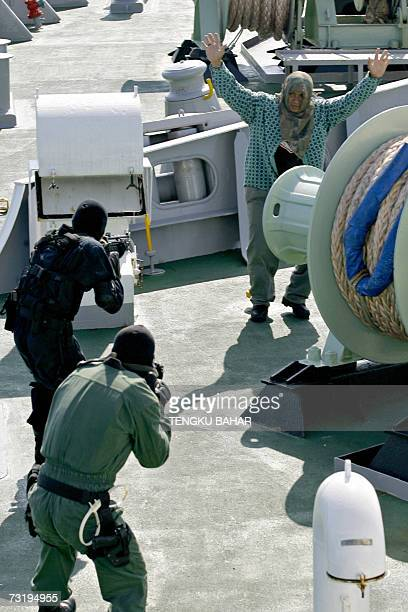 A 'pirate' surrenders to armed members of the Malaysian Police special forces units on board the Japanese Coast Guard ship Yashima during a joint...