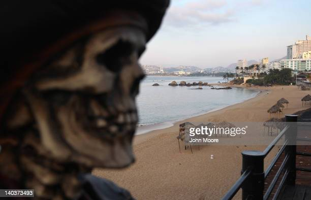 Pirate themed bar decor looms over an empty beach early on March 2, 2012 in Acapulco, Mexico. Drug violence surged in the coastal resort last year,...