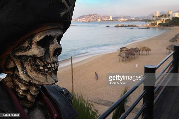 Pirate themed bar decor looms over an empty beach early on March 2 2012 in Acapulco Mexico Drug violence surged in the coastal resort last year...