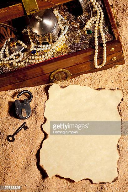 Pirate Treasure Chest and blank Paper buried in the sand.