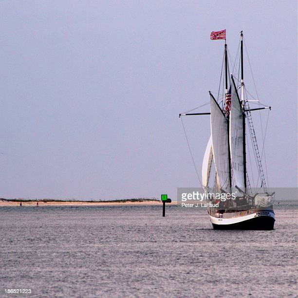 Pirate-ship charter on Matanzas River at the Saint Augustine inlet in northeastern Florida with full sails and outstretched flag. Beach sand, dunes,...