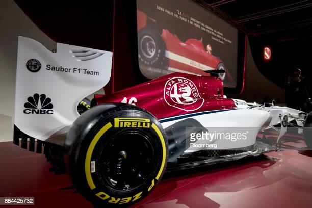 A Pirelli Co SpA tire sits on the rear axle of the Alfa Romeo Sauber Formula One racing car during a news conference at the Alfa Romeo Museum in...