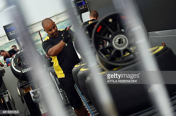 A Pirelli team member prepares a tyre in their base at the Hungaroring circuit in Budapest on July 23 2015 prior to the weekend's Hungarian Formula...