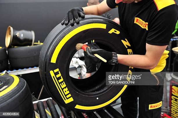 A Pirelli team member prepares tyres and rims in the paddock at the SpaFrancorchamps circuit in Spa on August 21 2014 ahead of the Belgium Formula...
