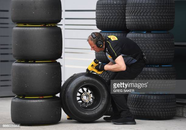 A Pirelli technician prepares tyres outside the Torro Rosso garage after a practice session for the Formula One Chinese Grand Prix in Shanghai on...