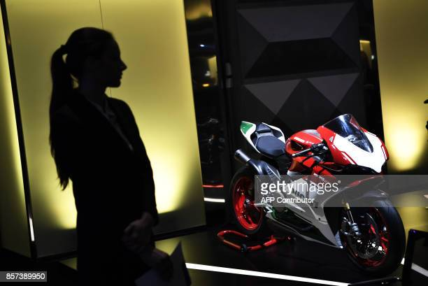 A Pirelli's hostess stands near a Ducati motorbike during a ceremony to mark the comeback of Italian tire maker Pirelli at Milan's stock on October 4...