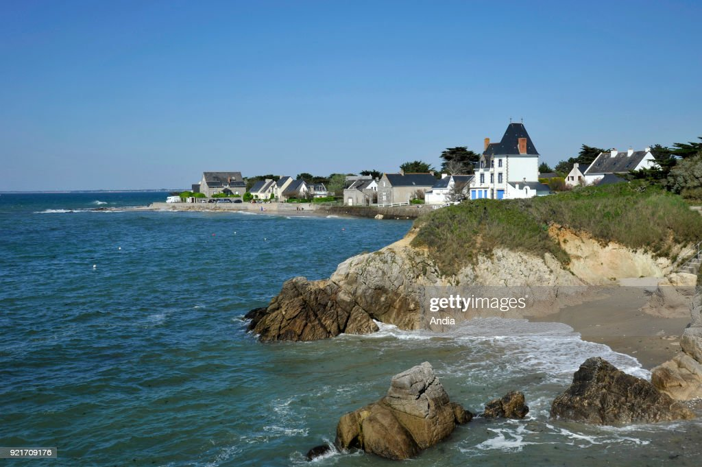 Piriac-sur-Mer (north-western France). : the rocky coast in the foreground and houses along the waterfront in the background viewed from the 'pointe du Castelli' headland.