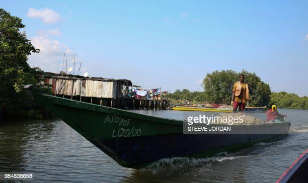 A pirogue speeds towards a fishermen's village outside Libreville called grande poubelle on June 21 2018 Foreign fishermen from Nigerians and...