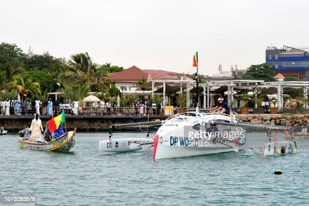 Pirogues escort the Row4ocean rowing trimaran as he leaves Dakar to cross the Atlantic on December 14 2018 A rowing trimaran took off on December 14...