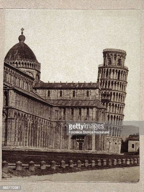Pisa, a view of the Cathedral and the leaning tower . In the photograph, the scaffolding on the tower suggests a restoration in progress....