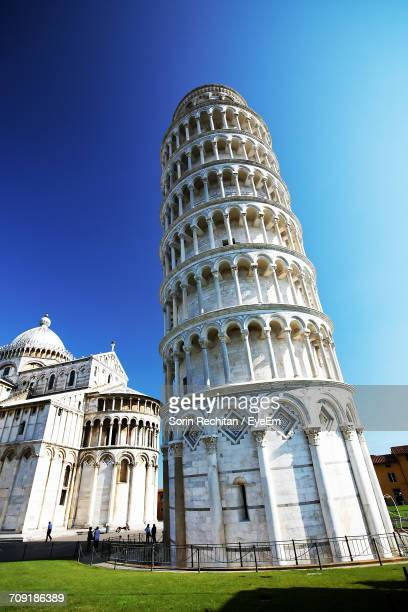 pisa cathedral by leaning tower against clear blue sky - monument stockfoto's en -beelden