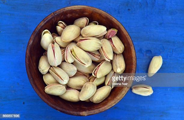 Pistachio nuts in a wooden bowl against blue background
