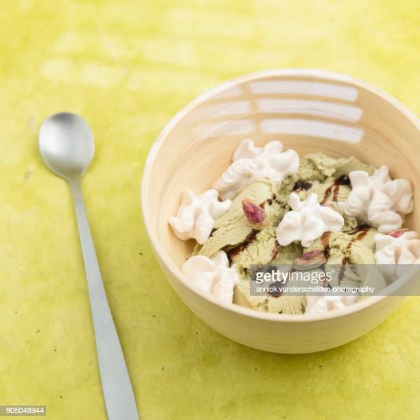 Pistachio scoop ice cream served in wooden bowl.