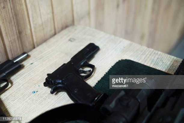 pistol on table in an indoor shooting range - armamento imagens e fotografias de stock