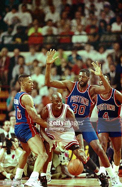 Pistons' Dennis Rodman Tree Rollins and Joe Dumars surround Bulls' Michael Jordan during the 3rd quarter 5/21 of game two of the Eastern Conference...