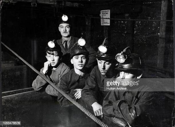 Pit boys with pit helmets and miners' lamps in a coal mine at Ashington Northumberland circa 1950