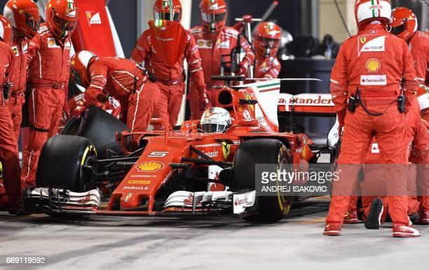 Pit crew and mechanics surround Ferrari's German driver Sebastian Vettel in the pit lane during the Bahrain Formula One Grand Prix at the Sakhir...