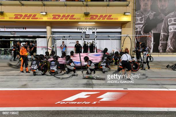 Pit crew and mechanics surround Force India's Mexican driver Sergio Perez in the pit lane during the Bahrain Formula One Grand Prix at the Sakhir...