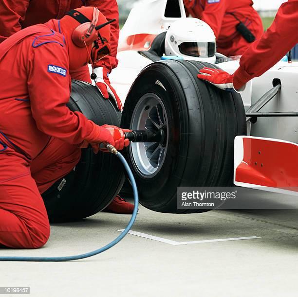 Pit crew changing racing car wheel