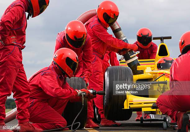 pit crew changing tire on formula one racecar - auto racing stock pictures, royalty-free photos & images