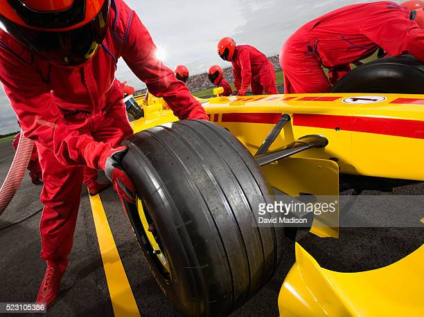 pit crew member changing tire on racecar - pit stop stock pictures, royalty-free photos & images