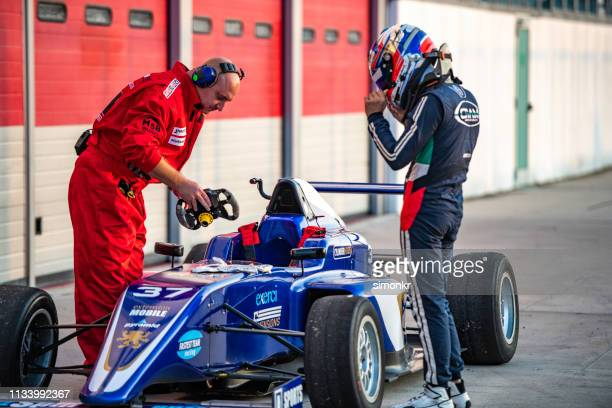 pit crew member holding steering wheel - pit stop stock pictures, royalty-free photos & images
