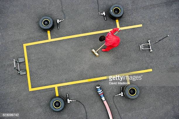 pit crew member sweeping pit box - pit stop stock pictures, royalty-free photos & images