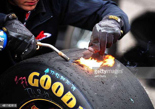 A pit crew member uses a blowtorch to inspect tire wear during practice for the NASCAR Camping World Truck Series Kroger 250 at Martinsville Speedway...