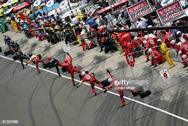 Pit crew members direct their drivers into the pit boxes during the IRL IndyCar Series 92nd running of the Indianapolis 500 at the Indianapolis Motor...