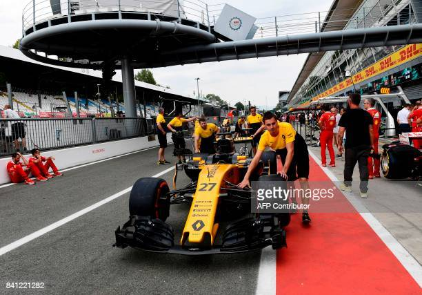 Pit crew members push Renault driver Niko Hulkenberg's race car at the Autodromo Nazionale circuit in Monza on August 31, 2017 ahead of the Italian...
