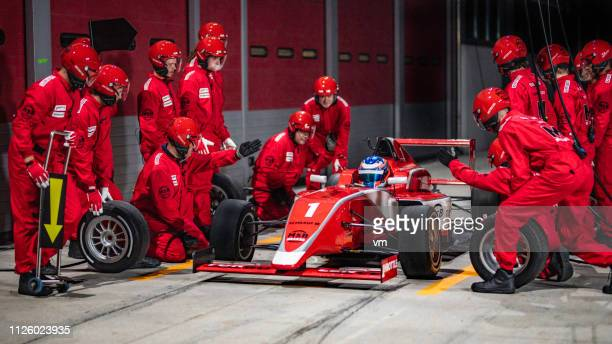 pit crew preparing to change tires on formula car - pit stop stock pictures, royalty-free photos & images