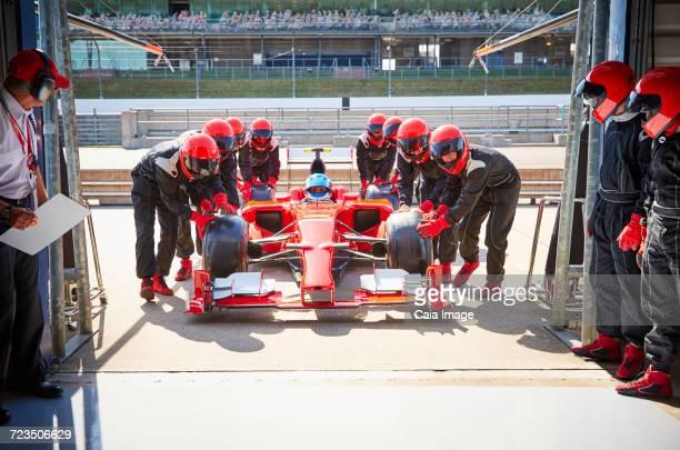 Pit crew pushing formula one race car into repair garage