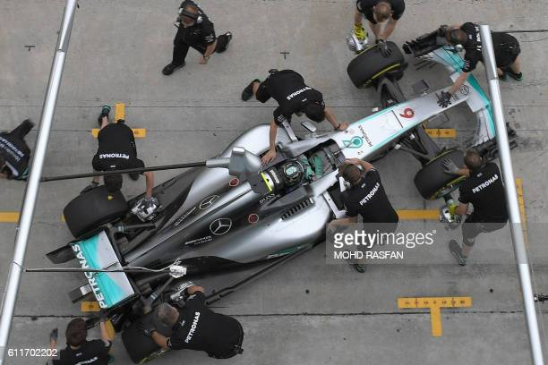 TOPSHOT Pit crew surround Mercedes AMG Petronas F1 Team's German driver Nico Rosberg's car during the qualifying session of the Formula One Malaysian...