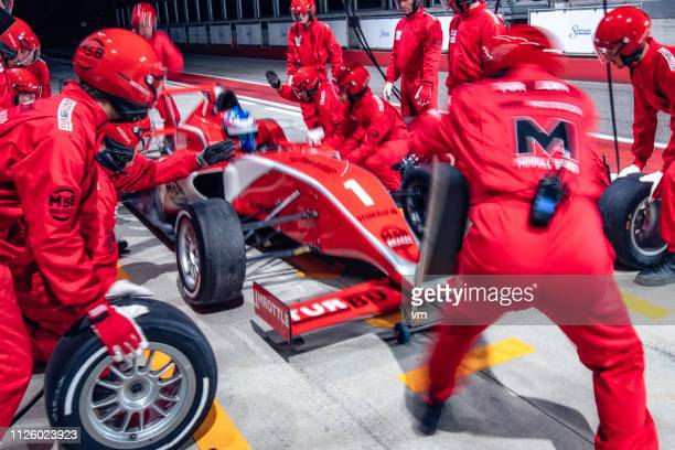 pit crew working on a red formula race car - auto racing photos stock pictures, royalty-free photos & images