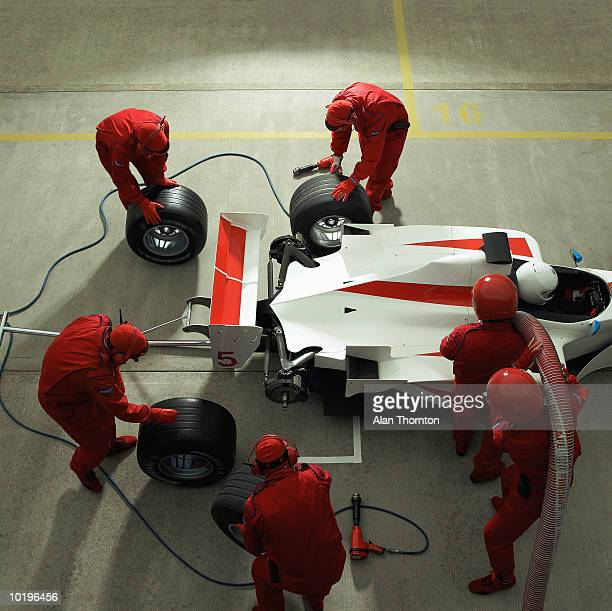 Pit crew working on racing car, elevated view
