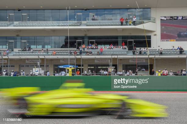 Pit crews watch from inside the track as cars race by just prior to the only caution of the race at lap 45 during the IndyCar Classic at Circuit of...