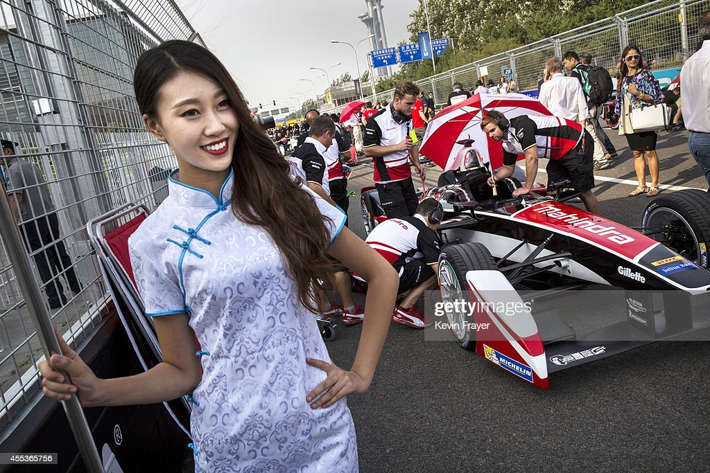 A pit girl stands next to a team car on the grid before the inaugral FIA Formula E Beijing ePrix Championship race on September 13, 2014 in Beijing, China. The electric car racing series is backed by many of the major sponsors of the main Formula One circuit, and is set to be hosted in nine other cities worldwide.