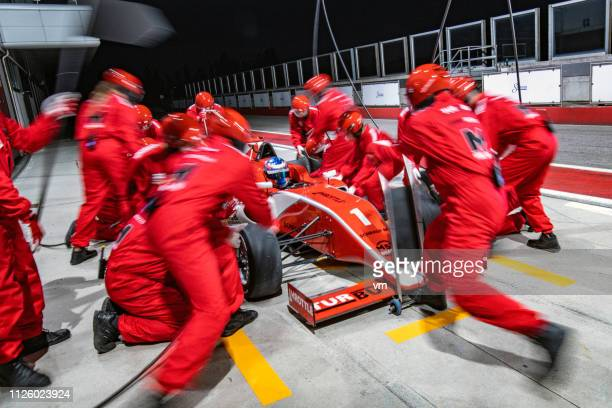 pit stop crew servicing a formula race car - pit stop stock pictures, royalty-free photos & images
