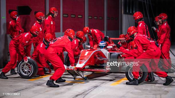 pit stop team working on a red formula race car - pit stop stock pictures, royalty-free photos & images
