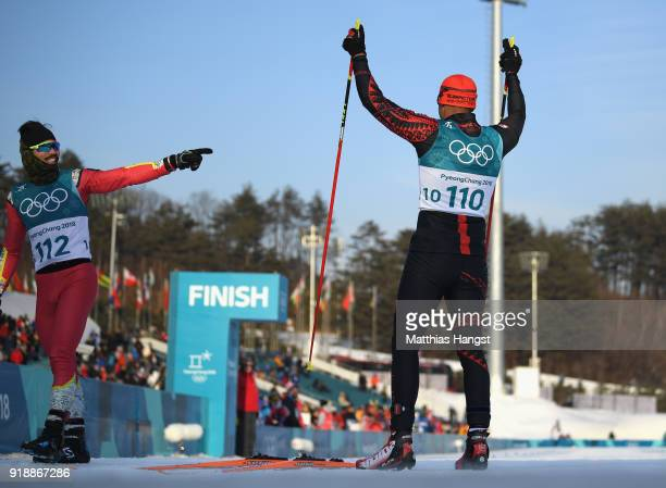 Pita Taufatofua of Tonga celebrates after crossing the finish line with Kequyen Lam of Portugal during the CrossCountry Skiing Men's 15km Free at...