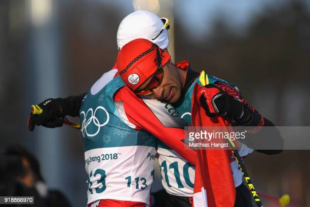 Pita Taufatofua of Tonga reacts with Samir Azzimani of Morocco after crossing the finish line during the CrossCountry Skiing Men's 15km Free at...