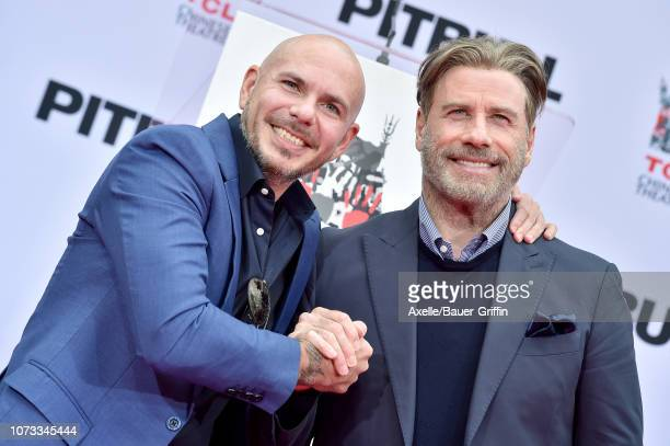 Pitbull and John Travolta attend the Hand and Footprint Ceremony honoring Pitbull at TCL Chinese Theatre on December 14 2018 in Hollywood California
