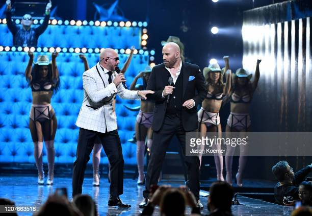 Pitbull and John Travolta perform live on stage during Univision's Premio Lo Nuestro 2020 at AmericanAirlines Arena on February 20 2020 in Miami...