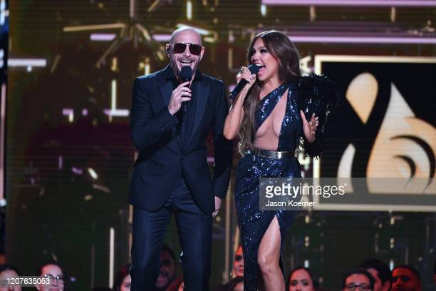Pitbull and Thalia speak on stage during Univision's Premio Lo Nuestro 2020 at AmericanAirlines Arena on February 20 2020 in Miami Florida