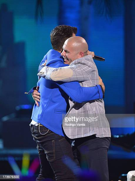 Pitbull greets Jencarlos Canela onstage during the Premios Juventud 2013 at Bank United Center on July 18 2013 in Miami Florida