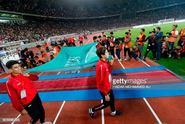 Pitch assistants walk out holding the Saudi Arabian flag prior to the start of the international friendly football match between Iraq and Saudi...
