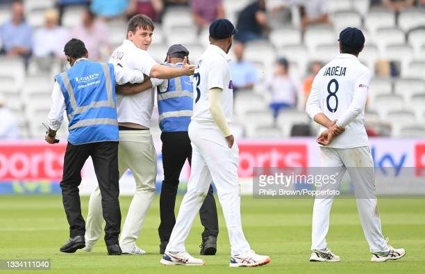 Pitch intruder dressed as a cricketer is escorted off the field during the third day of the 2nd LV= Test match between England and India at Lord's...