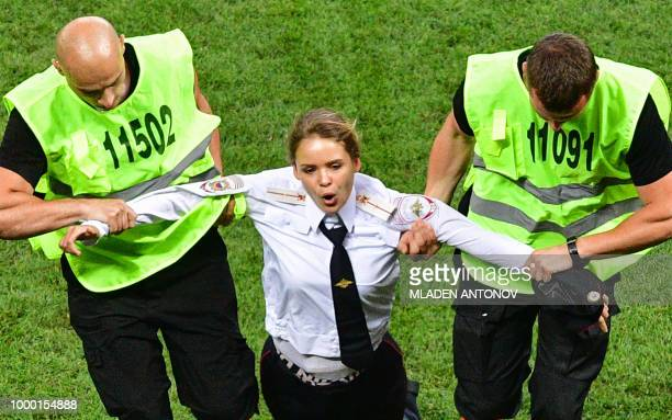 A pitch invader a member of the Russian protestart group Pussy Riot is escorted by stewards during the Russia 2018 World Cup final football match...