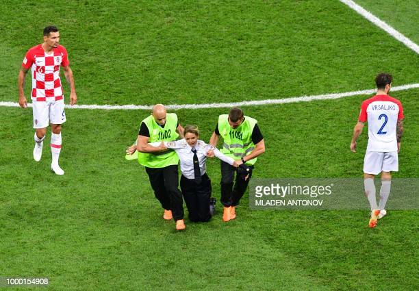 TOPSHOT A pitch invader a member of the Russian protestart group Pussy Riot is escorted by stewards during the Russia 2018 World Cup final football...